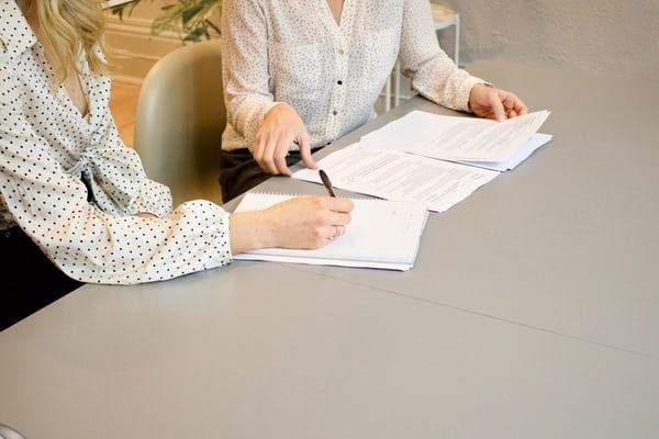 Two women sat at a table, one with a pen in hand about to sign a document.