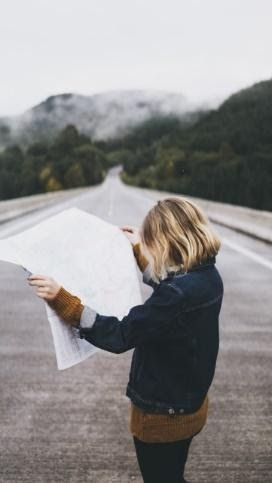 Woman reading a map on a road.