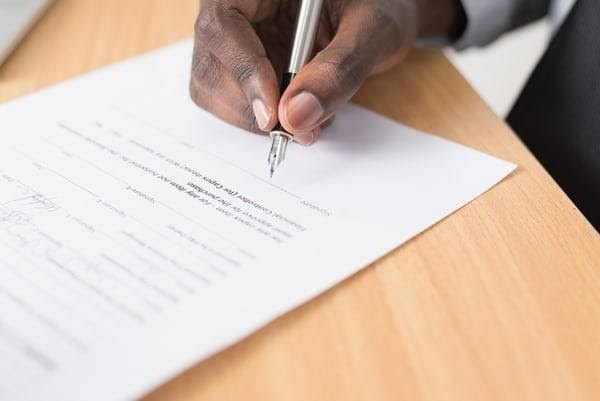 A hand with pen about to sign on paper.