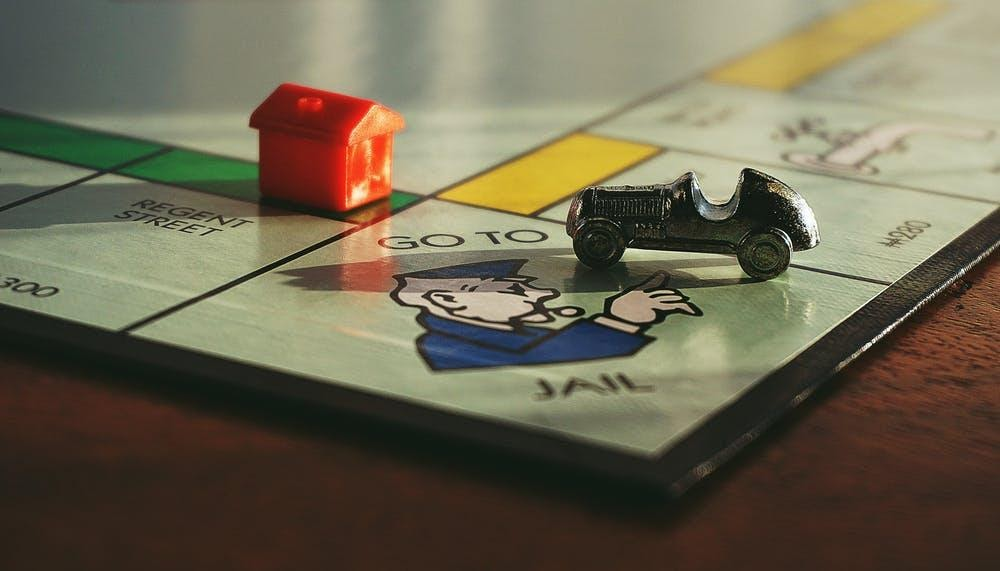 """A monopoly board showing the car piece and the house piece at the """"go to jail' section."""