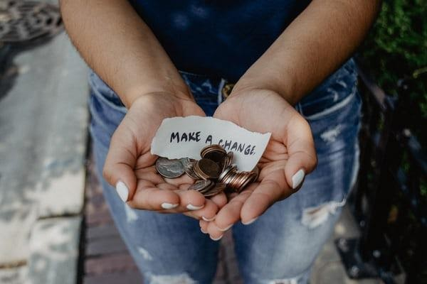"""Hand with coins with a note saying """"make a change""""."""