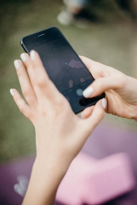 A persons hands on a phone.