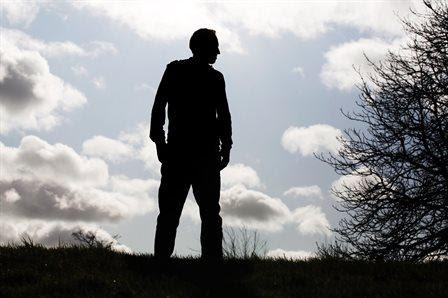 Silhouette of a man looking to the side with sky and clouds behind.