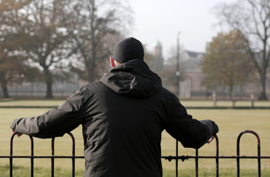 A man in a black coat and black hat with his back to the camera looking across a field.