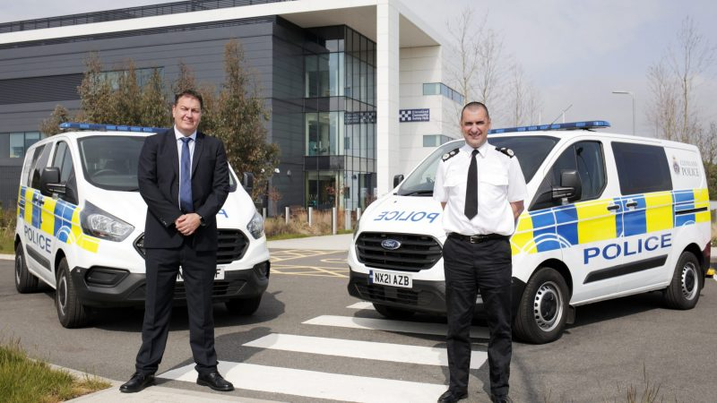 PCC Steve Turner and Chief Constable Richard Lewis stood in front of two police vans