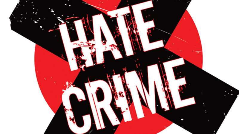 Hate Crime logo with a black cross on a red circle.