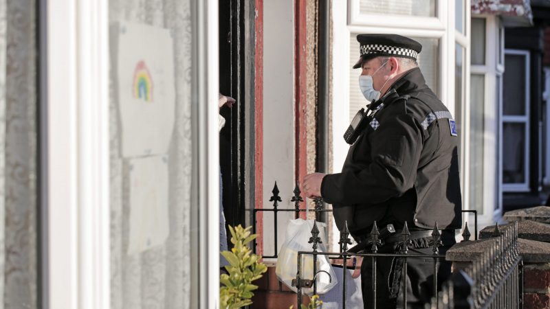 A police officer in uniform stands on a doorstep speaking to an unseen resident